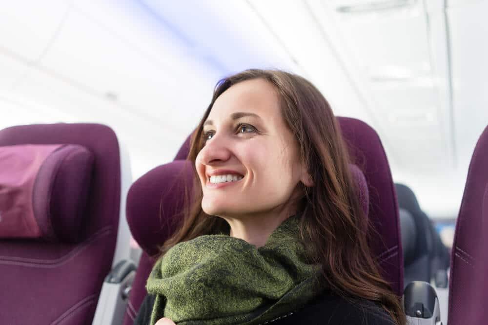 mulher com cachecol verde sentada num aviao