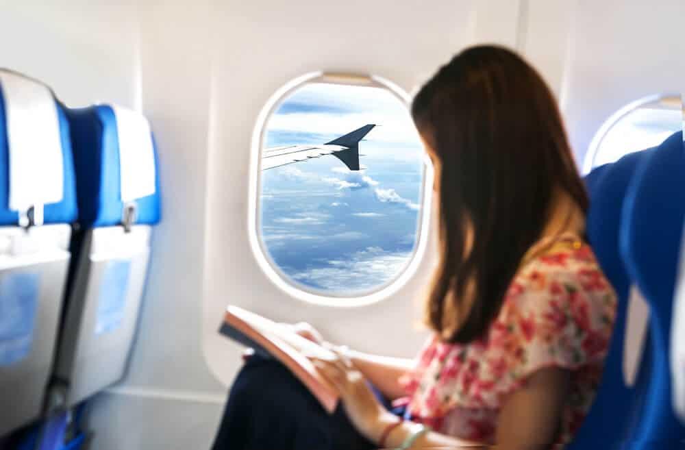 mulher sentada na janela do aviao a ler