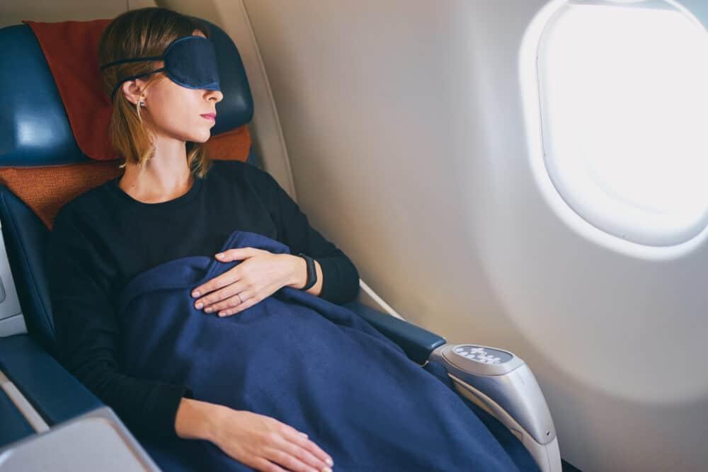 mulher deitada com manta e mascara num aviao