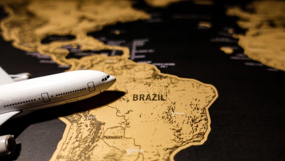 avião sobre mapa dourado do brasil