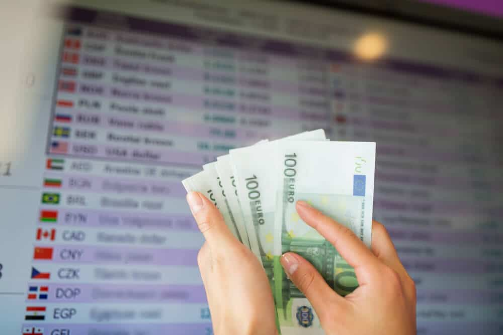 pessoa com notas de 100 euros e placard de taxas de cambio