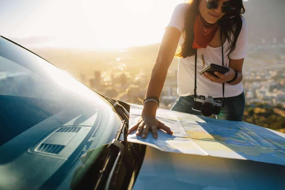 mulher a consultar um mapa em cima de um carro