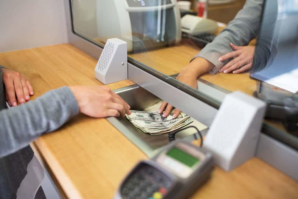 pessoa a cambiar dinheiro num banco