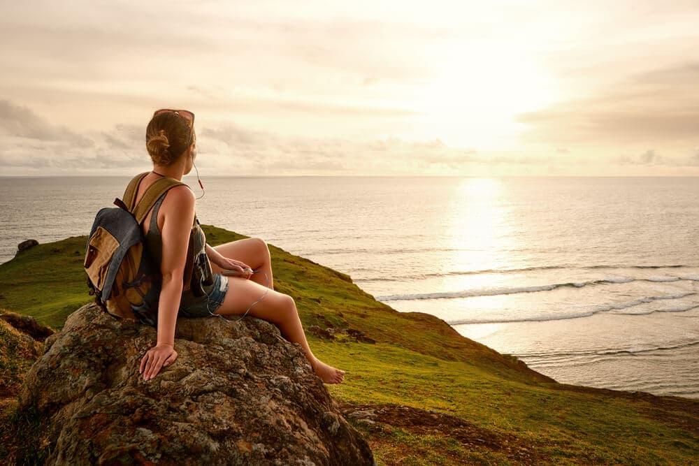 mulher a olhar para o horizonte sentada numa arriba