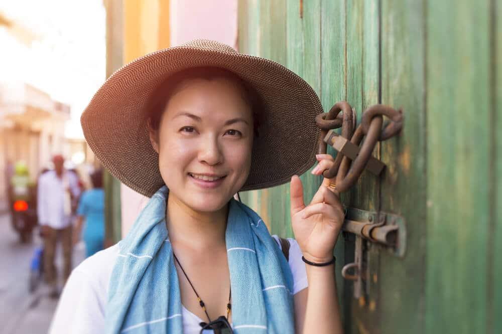 mulher asiatica a posar junto a porta verde