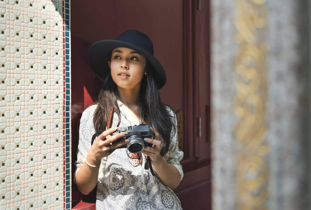 mulher com camara fotografica e chapeu preto