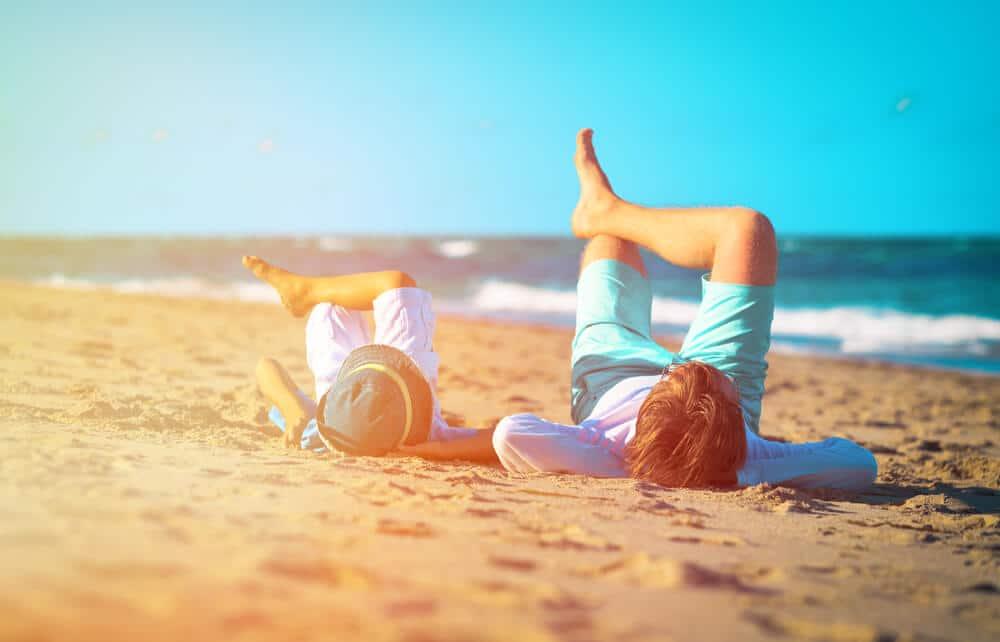 duas crianças deitadas na areia