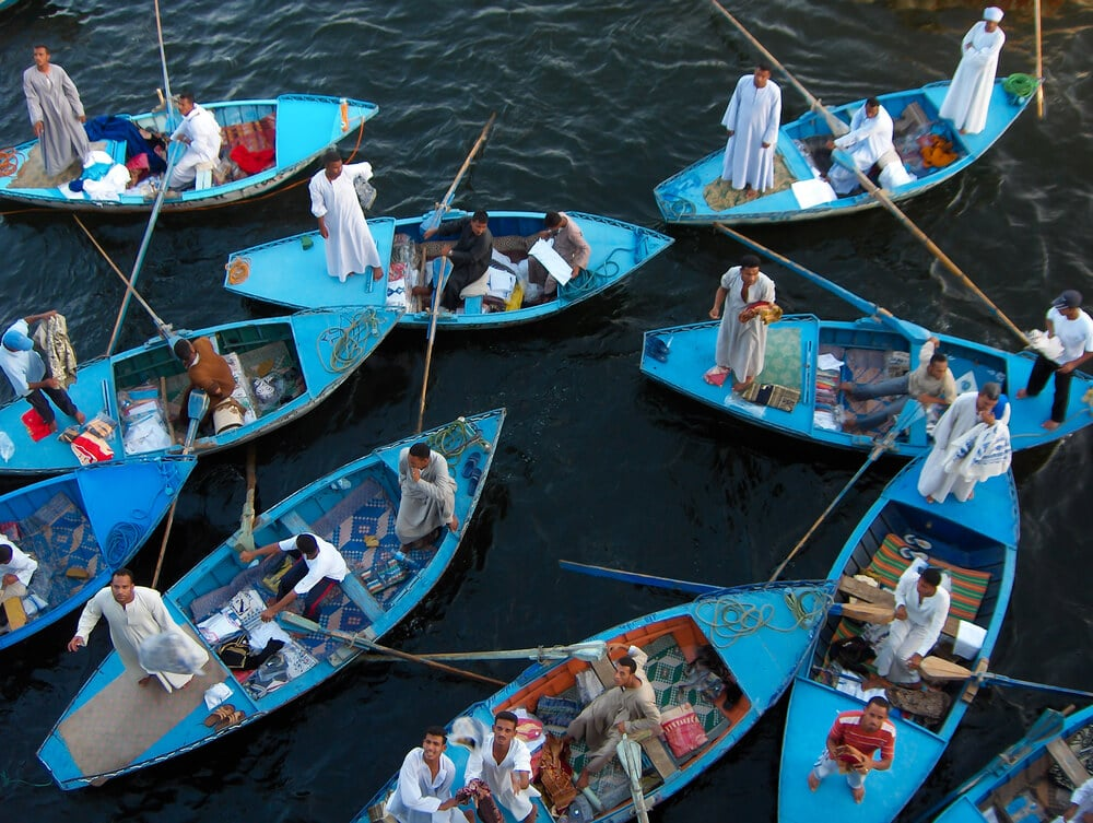 vendedores em pequenos barcos azuis no nilo