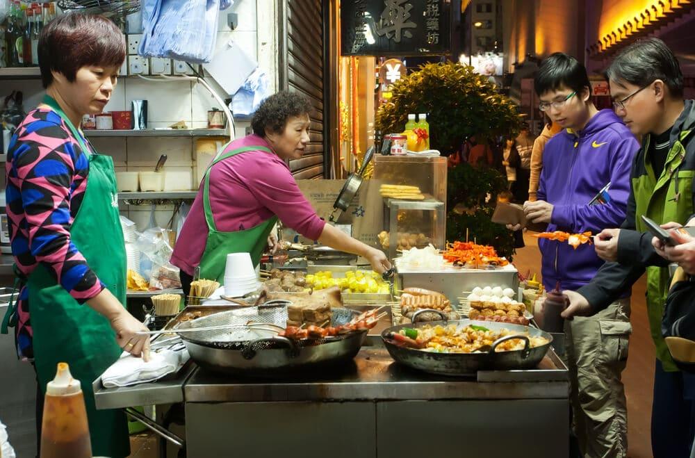 turistas vêm como se cozinham pratos típicos nas ruas de hong kong