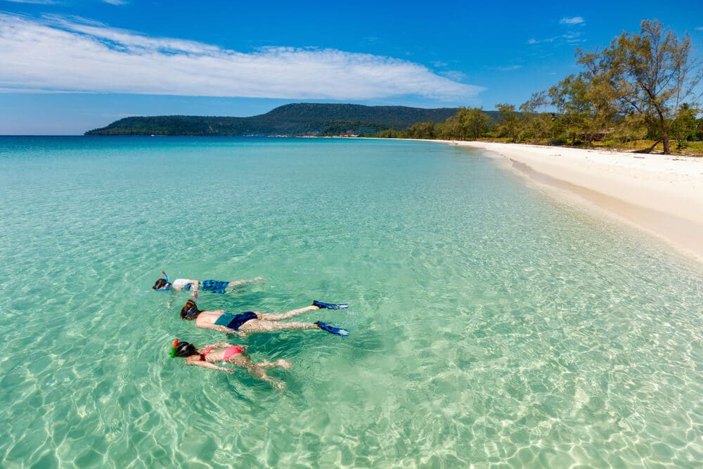 mães e dois filhos a fazer snorkeling em aguas cristalinas