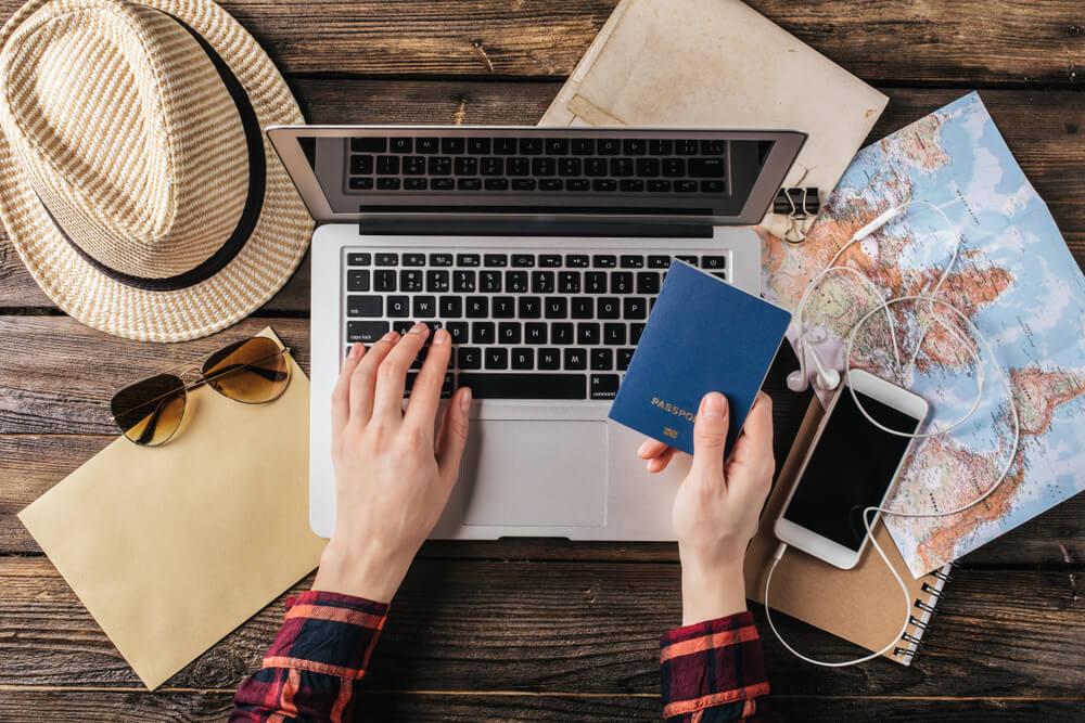 pessoa com passaporte na mao e a mexer no computador