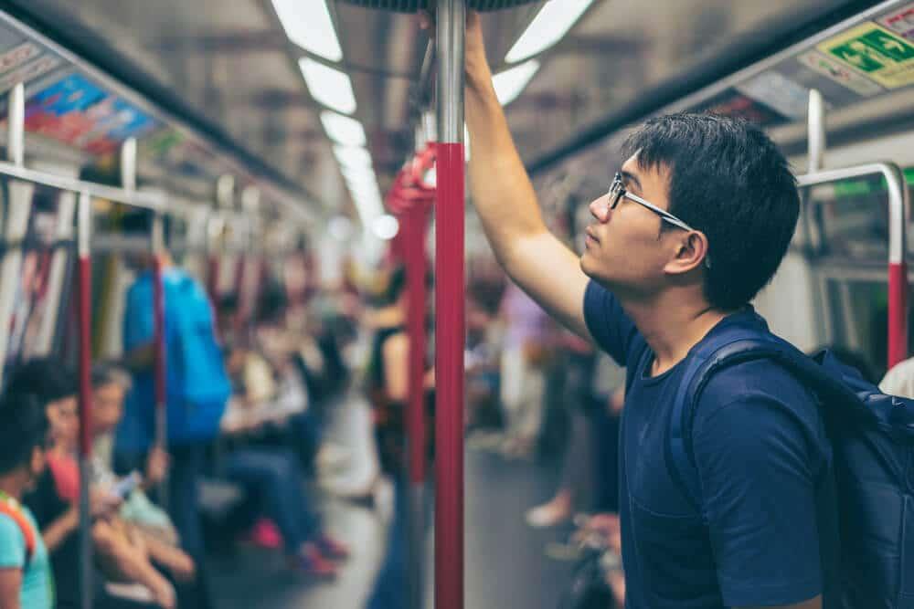 rapaz com óculos azuis de pé num metro de hong kong