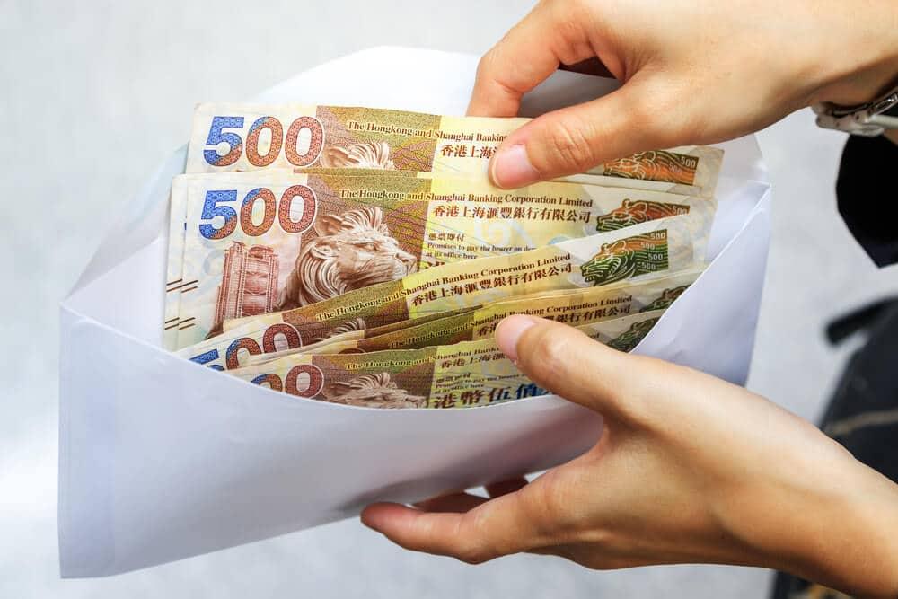 mãos a segurar envelope com quatro notas de 500 dolares de hong kong