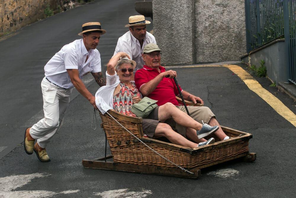 dois homens empurram um carro de cesto com turistas