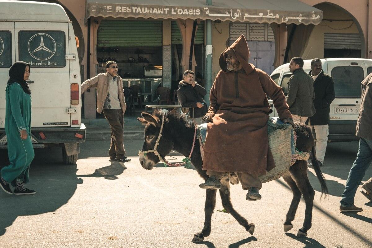 homem num burro chega ao mercado de rissani