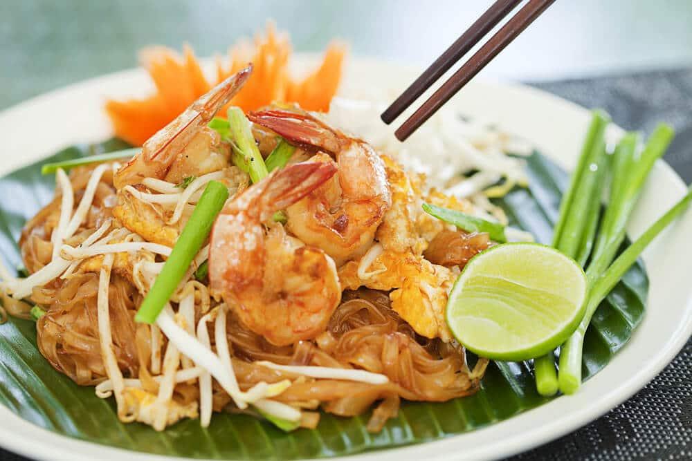 prato de comida tailandesa com pauzinhos ao fundo