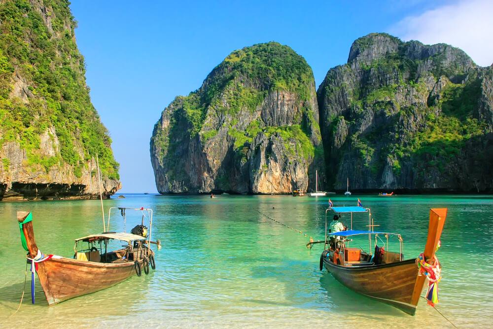 dois barcos numa praia tailandesa num dia solarengo