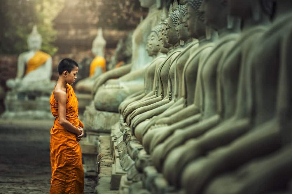 monge budista a rezar em frente a varias estatuas