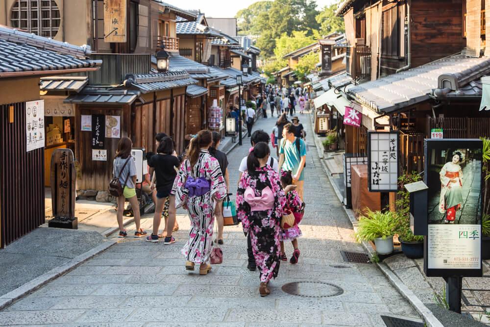 mulheres passeiam por gion vestidas com quimonos