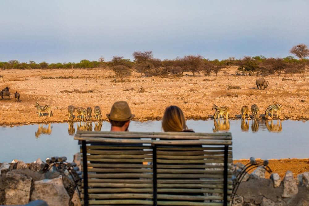 dois turistas a olhar para um lago na namibia