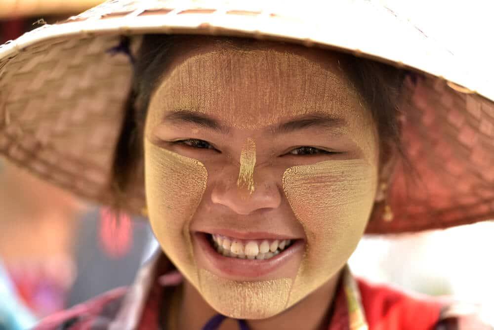 jovem de etnia burma sorri com chapeu de palha tipico