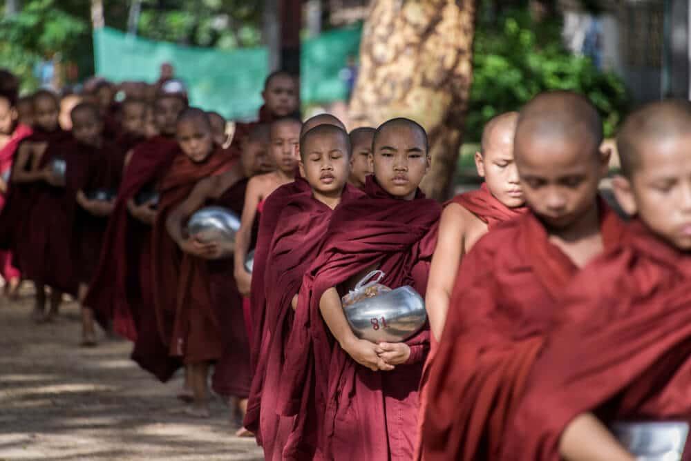 jovens monges em fila com oferendas