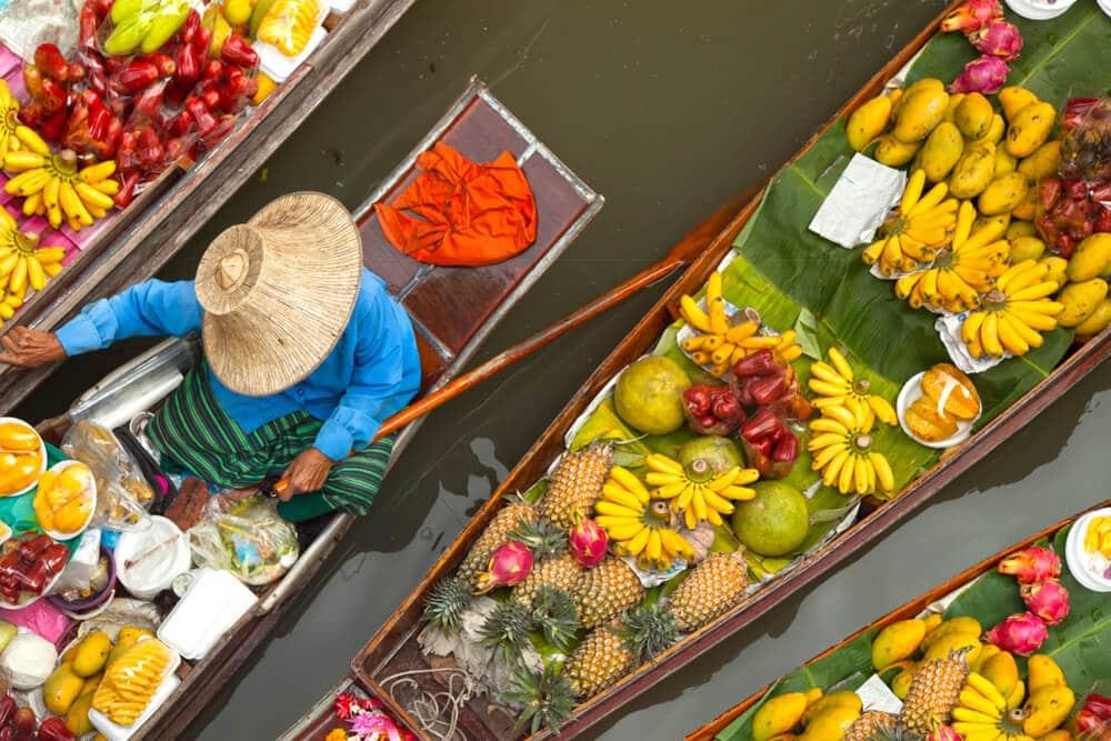 mulher a vender fruta num barco no mercado flutuante
