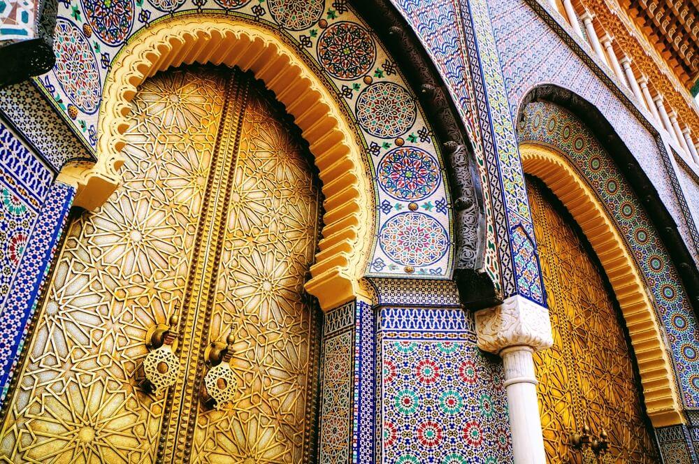 edificio de azulejos azuis com portas douradas fechadas em marrocos