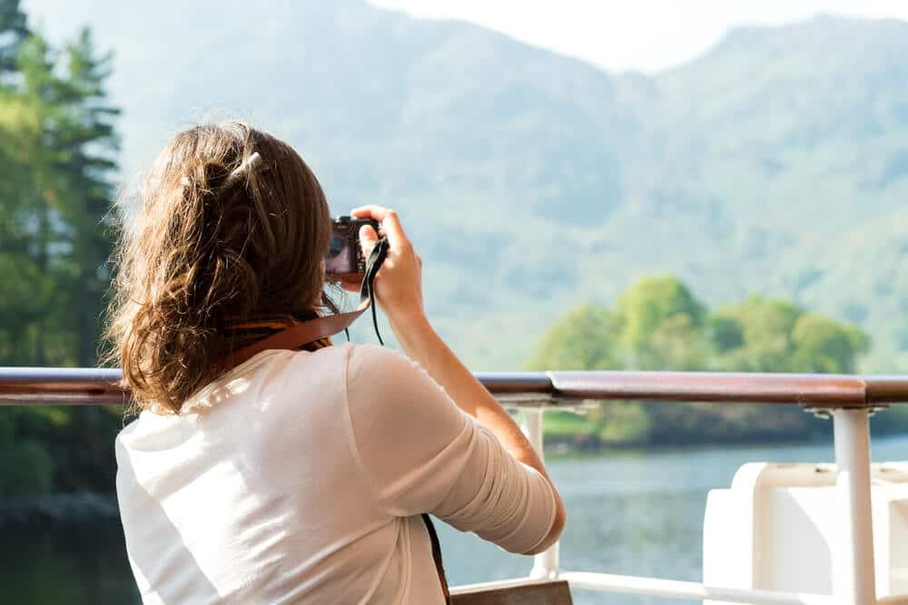 mulher de camisa branca tira fotos desde um barco às montanhas