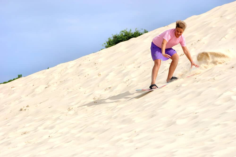 rapaz numa duna a praticar sandboard