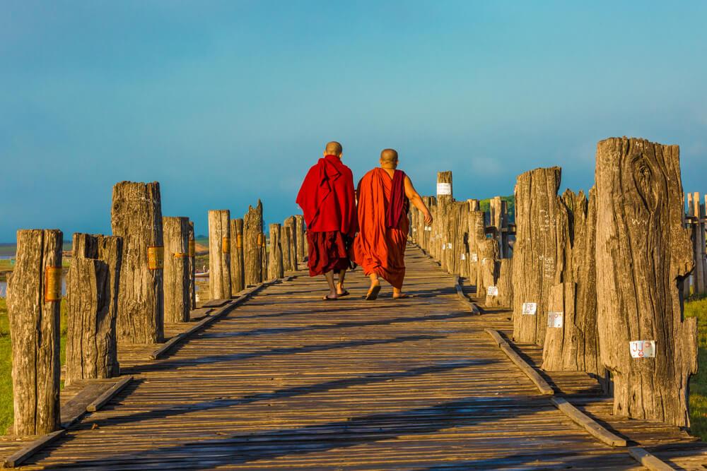 dois monges caminham numa ponte de madeira