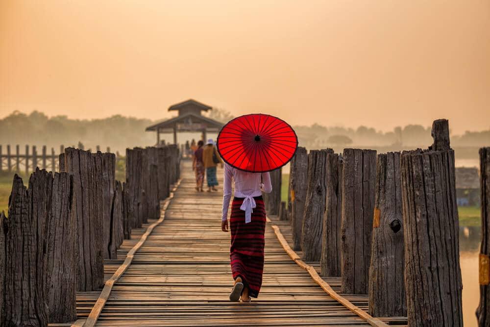 mulher de costas passeia numa ponte de madeira