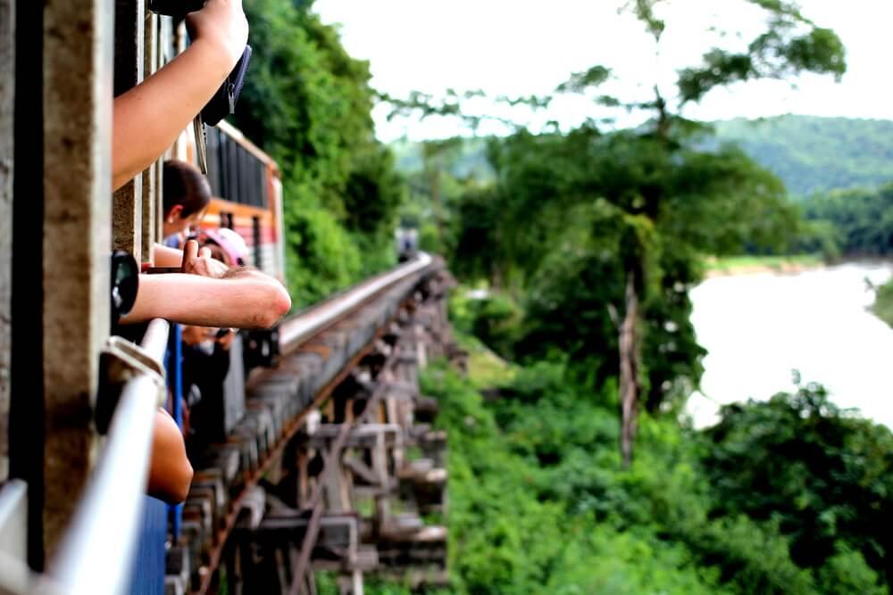 turistas apoiados na janela do comboio a tirar fotos