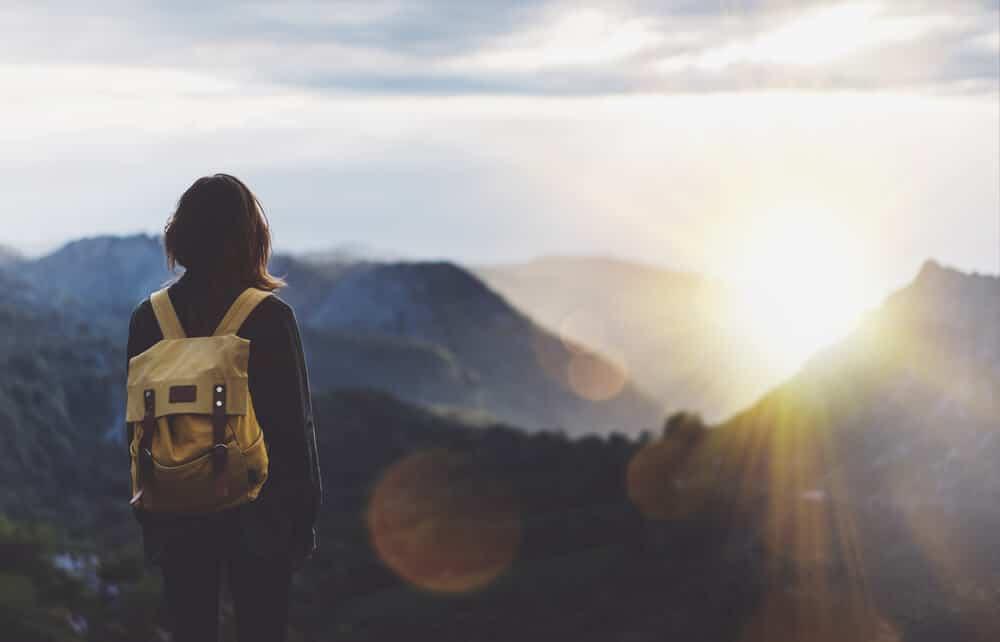 rapariga com mochila as costas olha para o horizonte
