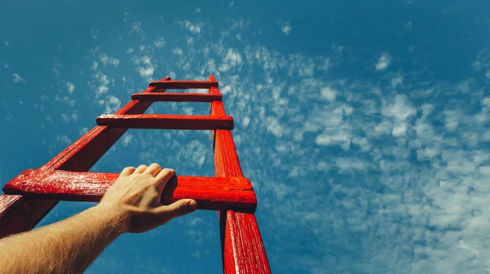 maos sobre escada vermelha em direção ao ceu