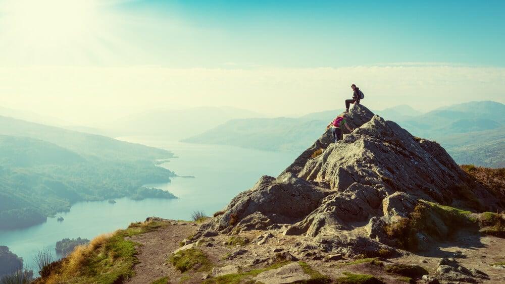 pessoa sentada no topo de uma montanha a contemplar o horizonte