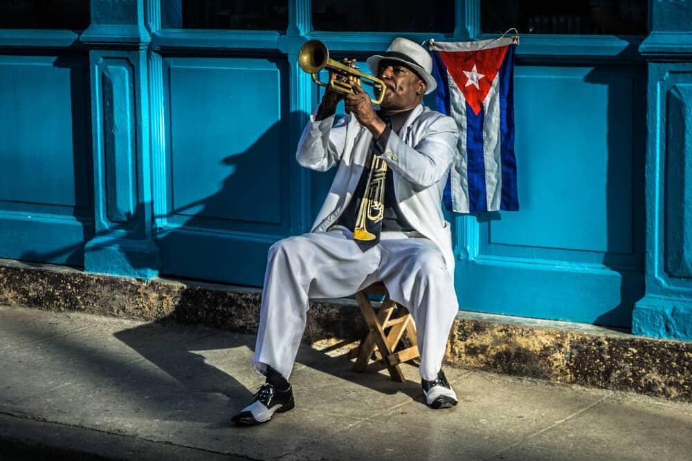 homem de fato a tocar trompeta com bandeira cubana por trás