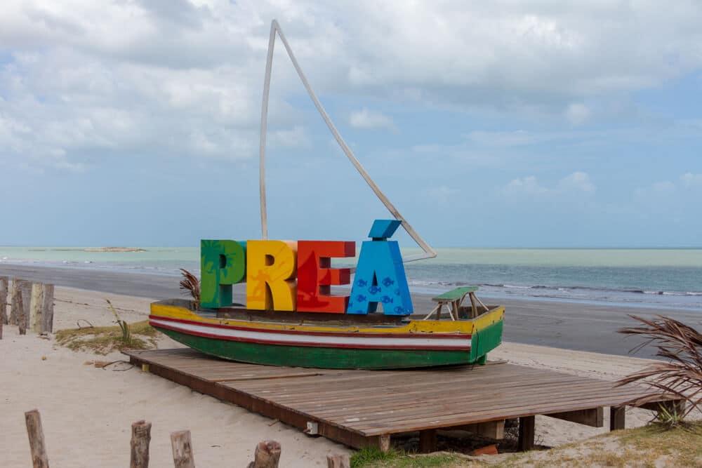 barco atracado com letras que formam a palavra Preá e mar no fundo