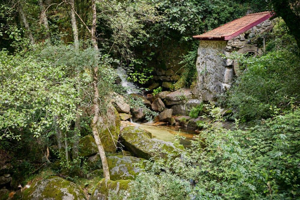 detalhes da aldeia de pontido, com uma casa de pedra e um riacho a descer