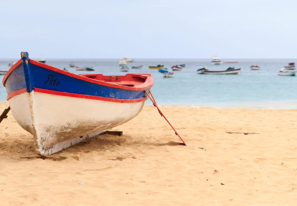 barco branco, azul e vermelho pousado no areal da praia de santa maria