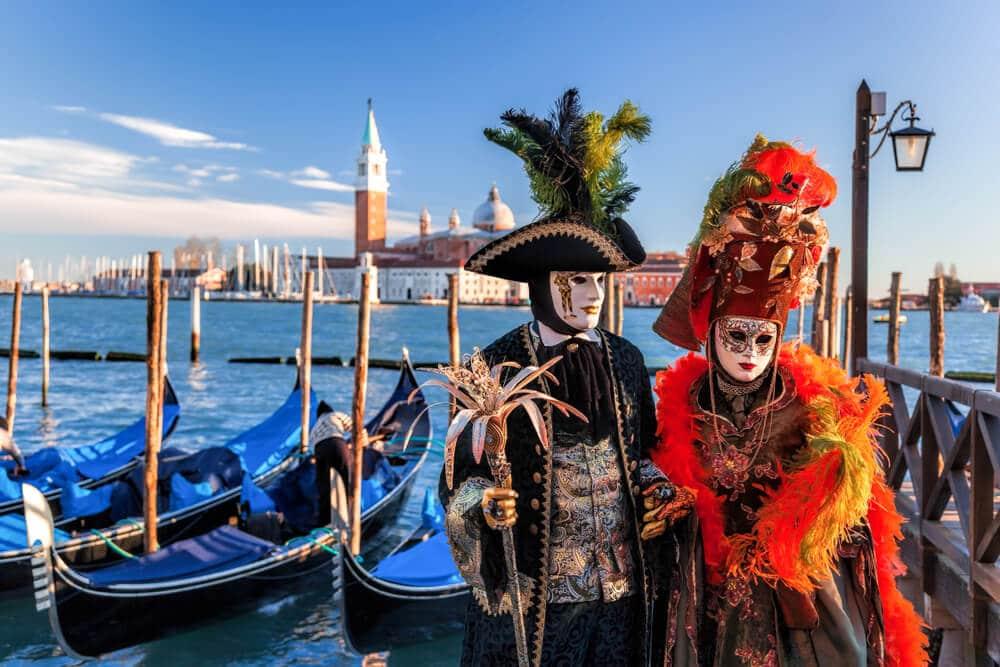 duas pessoas vestidas com trajes de carnaval posam em frente às gondolas e a um dos canais de veneza