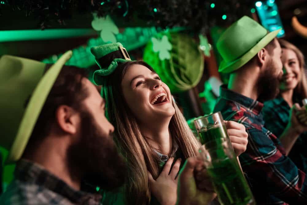 jovens com chapeus verdes riem e bebem cerveja