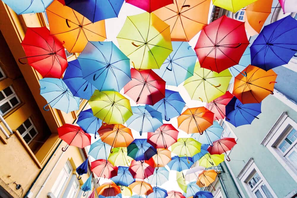 guarda-chuvas de varias cores pendurados sob uma rua de agueda