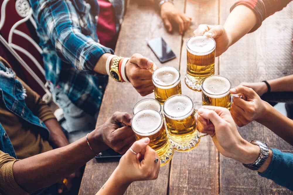 varios jovens a segurar canecas de cerveja sobre mesa de madeira