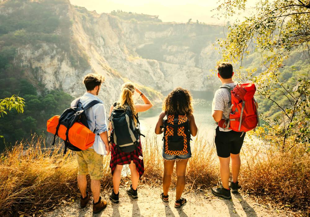 quatro jovens mochileiros olham para um rio desde uma montanha