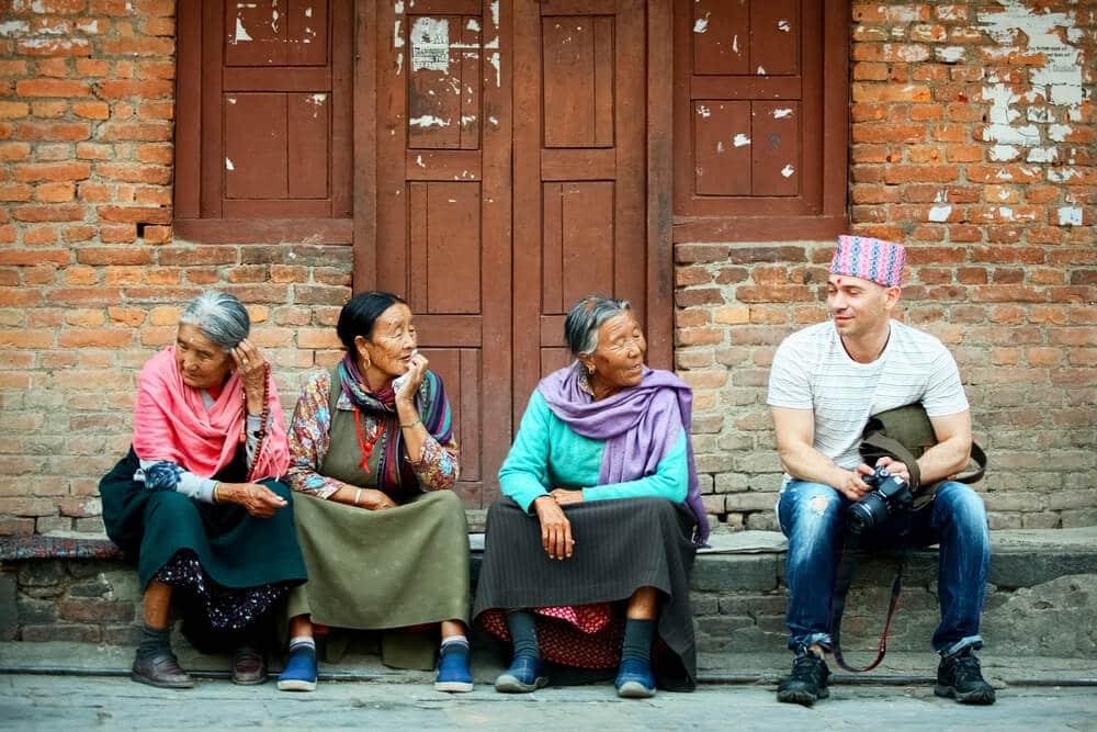 turista a falar com três locais sentados numas escadas