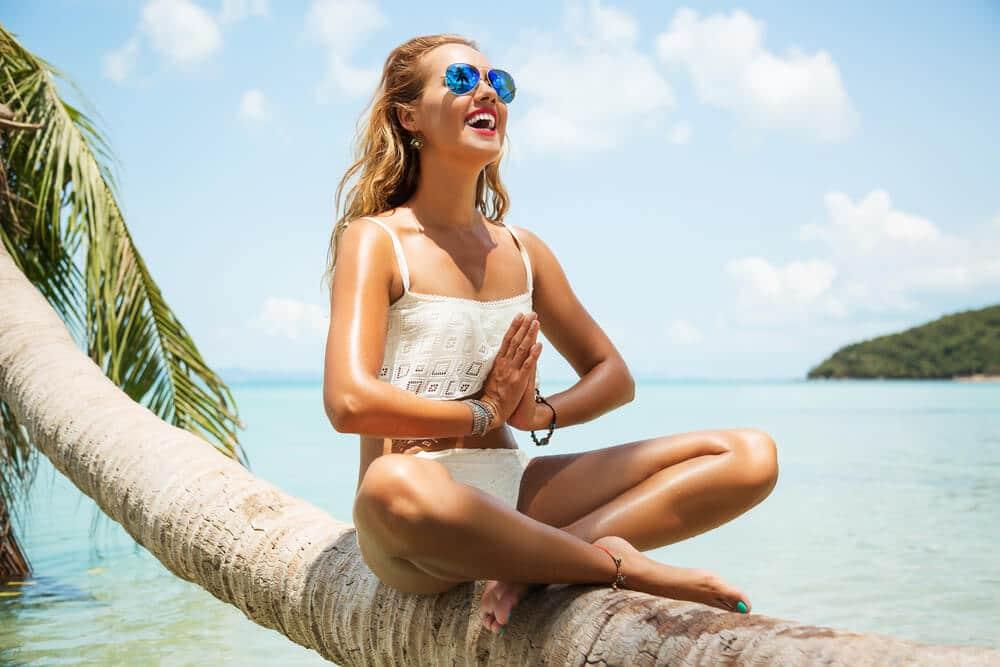 mulher jovem a meditar sentada numa palmeira na praia