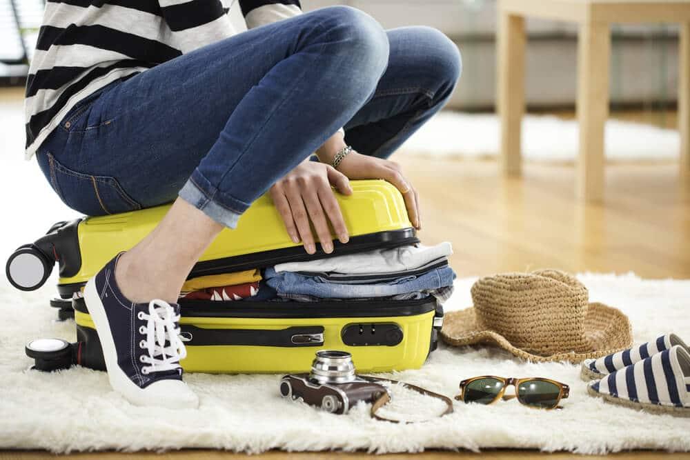 mulher sentada em cima de mala amarela para a fechar