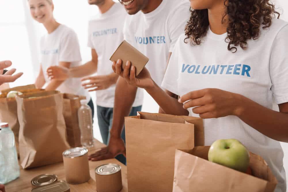 jovens com camisolas de voluntarios empacotam comida