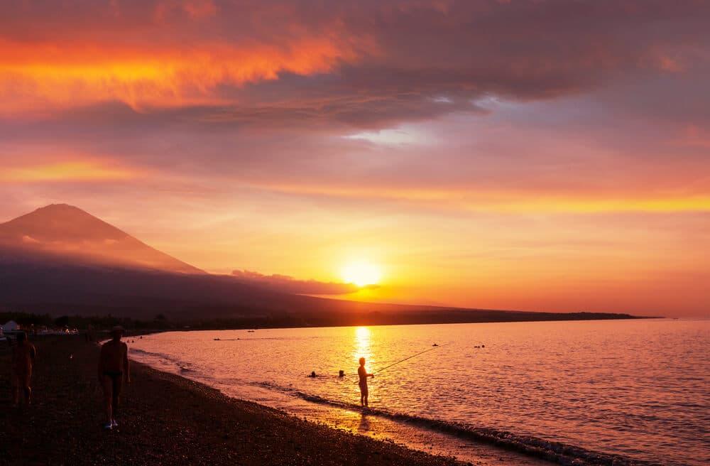 pessoa a pescar na praia de amed e vulcao agung ao por do sol